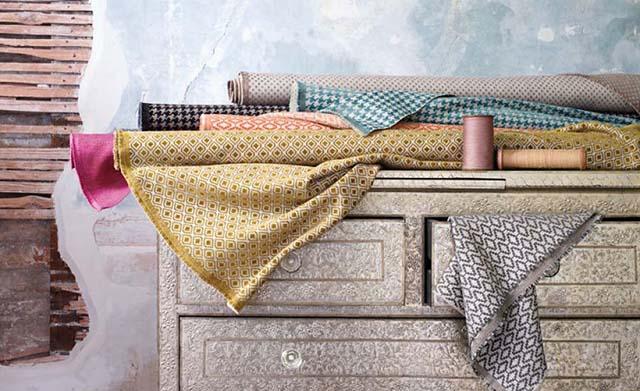 Rollos de telas de colores estampadas sobre cajonera de madera