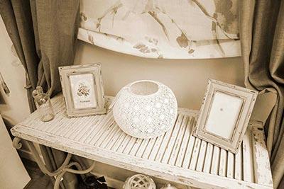 Mesa pequeña de madera con dos marcos de fotos y un portavelas