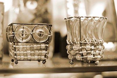 Dos portavelas hechos con alambre y vidrio. Imagen en sepia