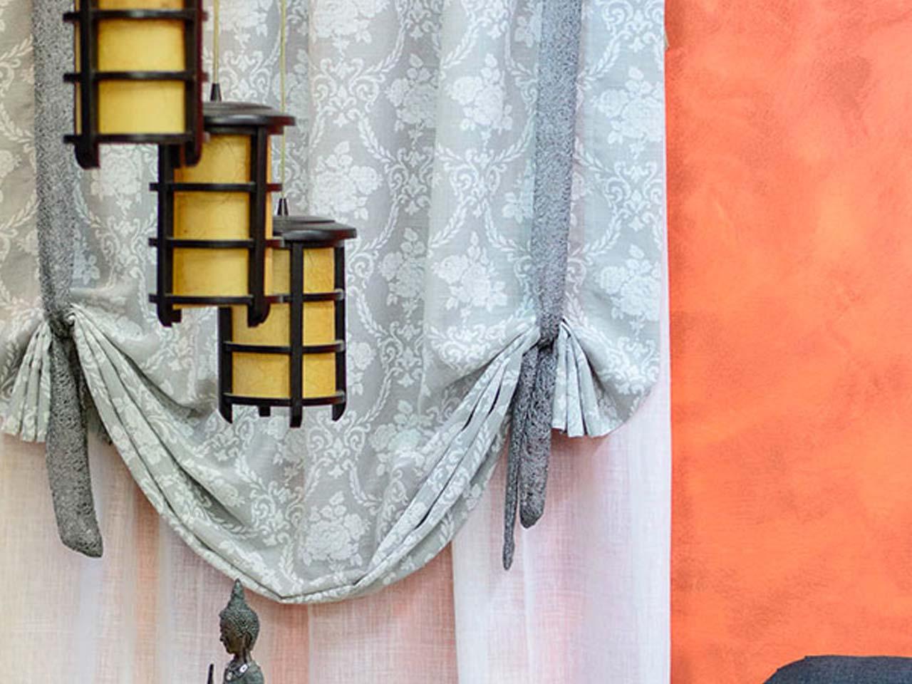 Cortines plegables grises sobre paret taronja amb fanals davant