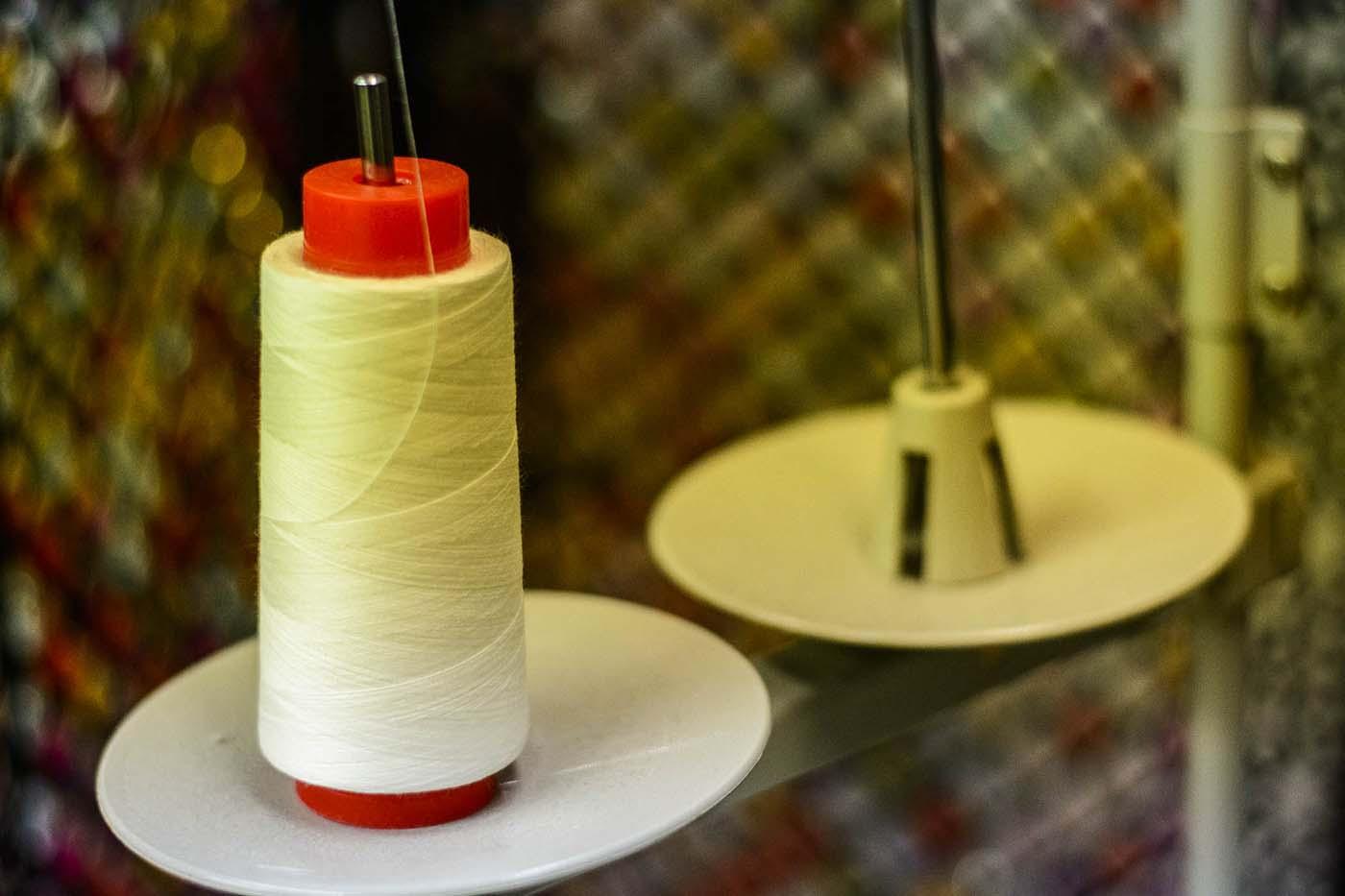 Bobina de fil blanc en porta fil de màquina de cosir