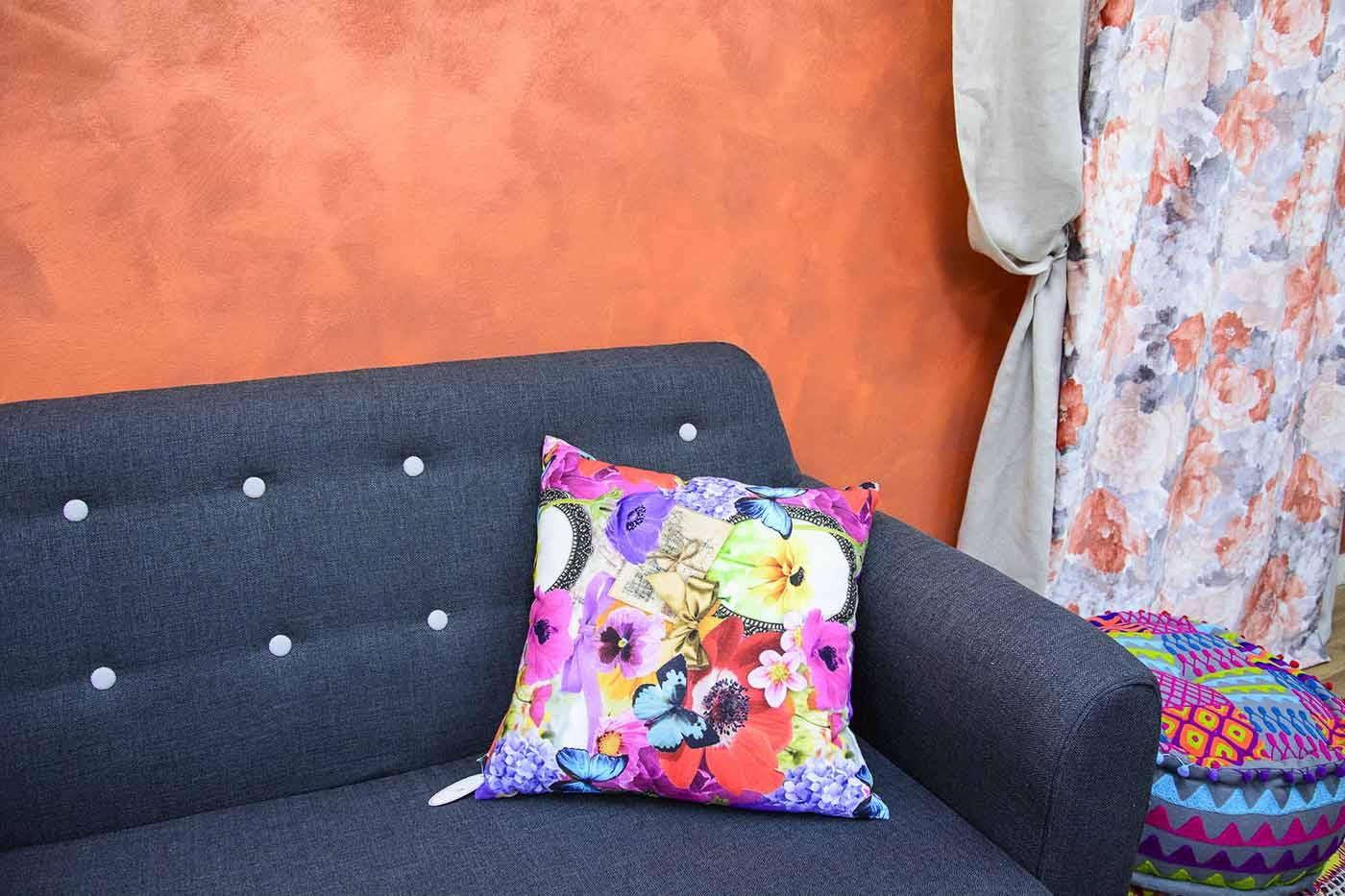 Sofà negre amb coixí de fons paret taronja i cortines