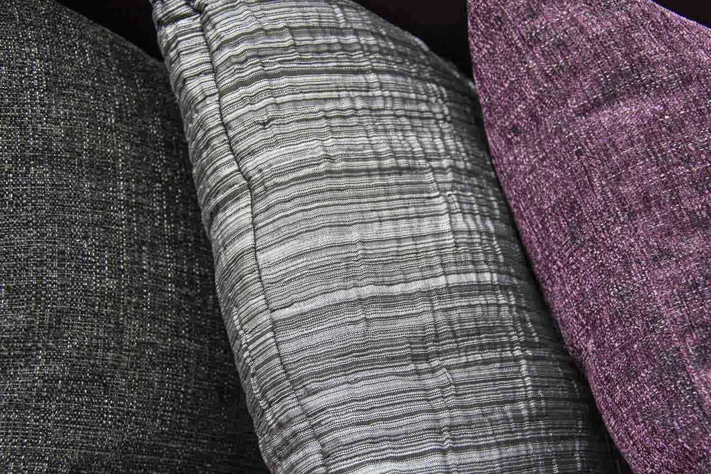 Detall tres coixins gris, gris clar i lila