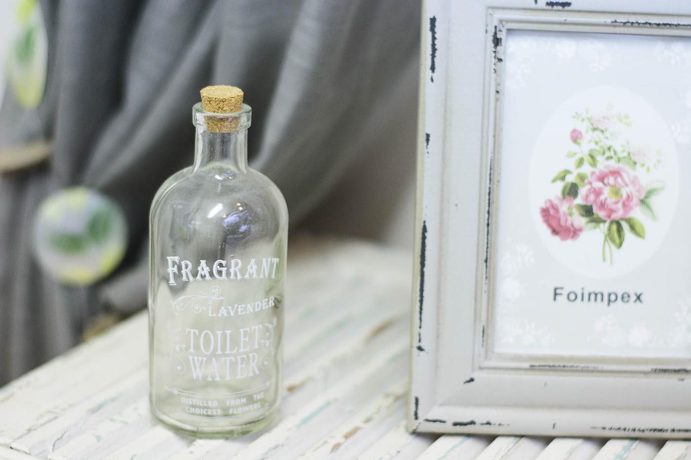 Botella transparente y portafotos vintage blanco sobre madera blanca