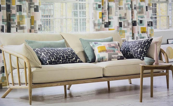 Primer plànol de sofà amb coixins estampats cortines estampades de colors