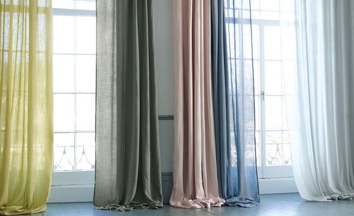 Finestra gran amb cortines llargues de diferents colors