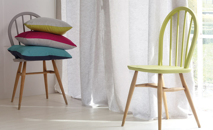 Finestra amb cortines blanques dues cadires de colors amb coixins de colors