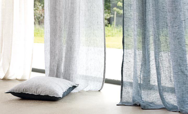 Primer plànol de finestra amb cortines de colors i coixí