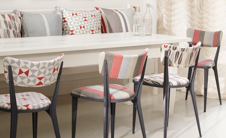Quatre cadires tapissades de colors amb taula blanca i coixins de colors