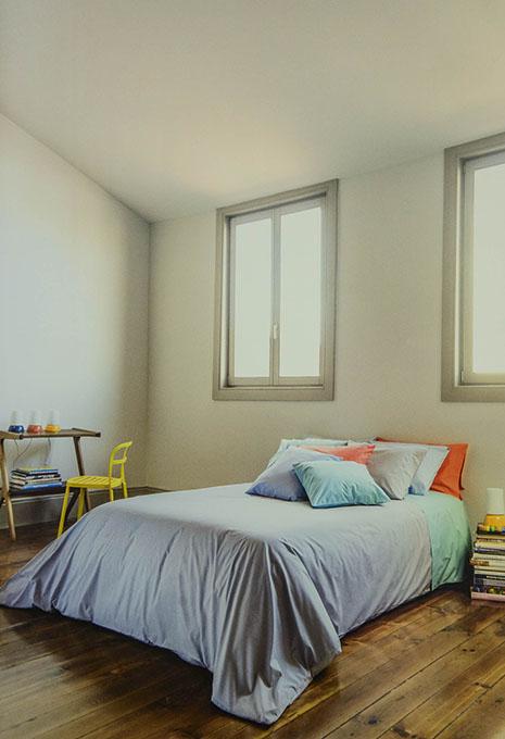 Habitació lluminosa amb llit edredó blau i coixins de colors