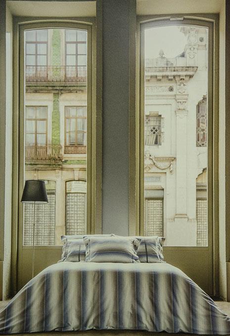 Llit amb edredó i coixins a ratlles finestra amb vistes