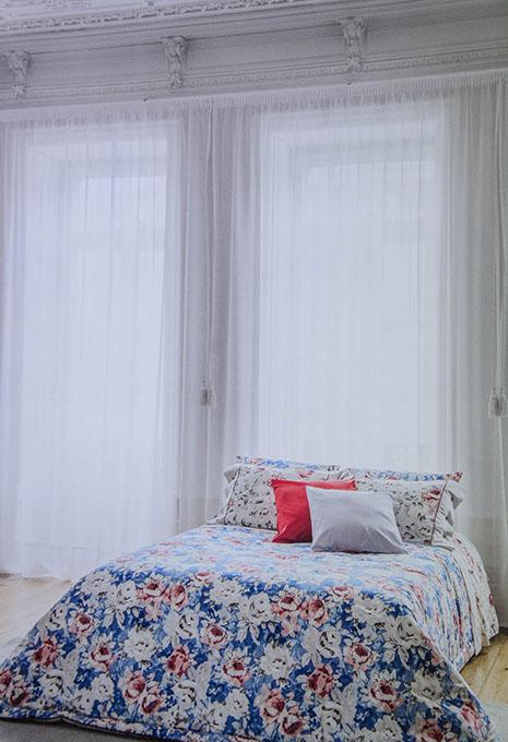 Llit amb edredó i coixins amb flors en habitació grans finestres
