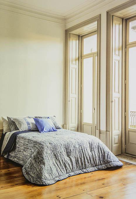 Llit amb edredó i coixins en habitació gran amb llum natural