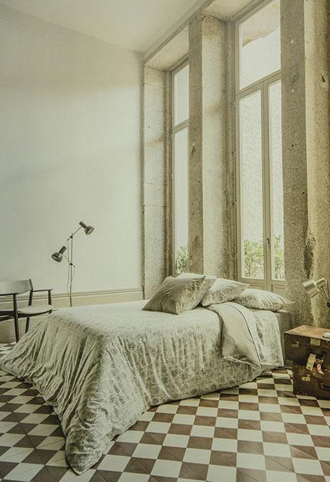 Llit amb edredó i coixins en habitació amb grans finestres