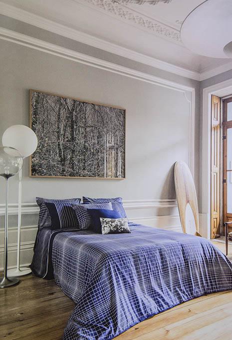 Llit amb edredó i coixins blaus en habitació àmplia sòl de fusta