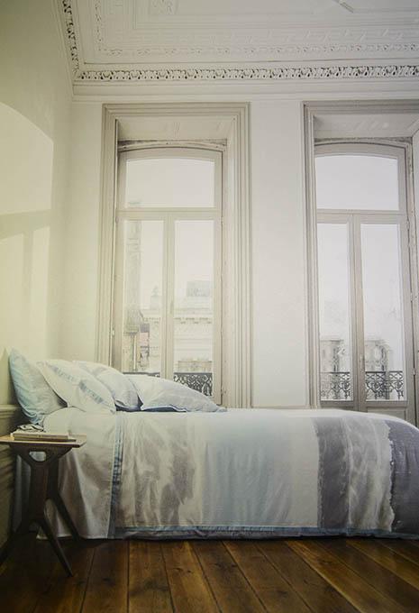 Llit edredó i coixins de colors càlids en habitació àmplia