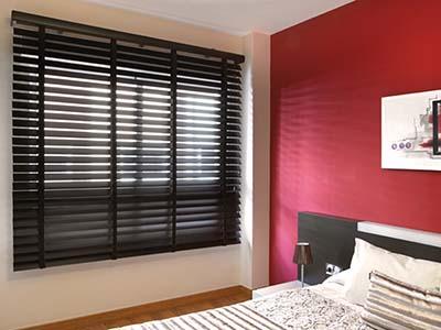 Habitación con cama y ventana con cortina veneciana