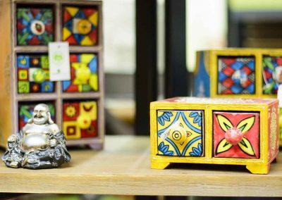 Detall d'aparador amb tres calaixeres miniatures de colors i petit buda