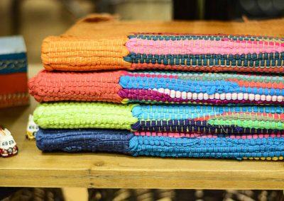Teixits rústics de colors apilats en taula de fusta