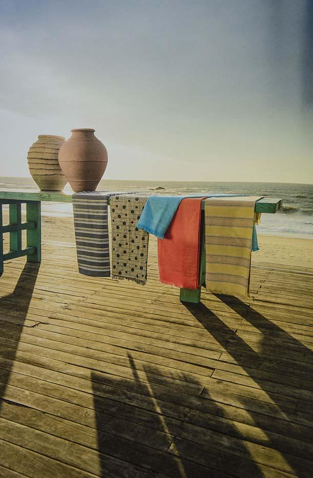 Catifes de colors penjades en barana amb gerros enfront del mar
