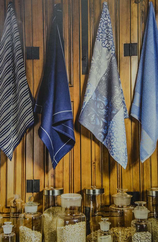 Draps de cuina tons blaus penjats en fusta sobre pots de vidre