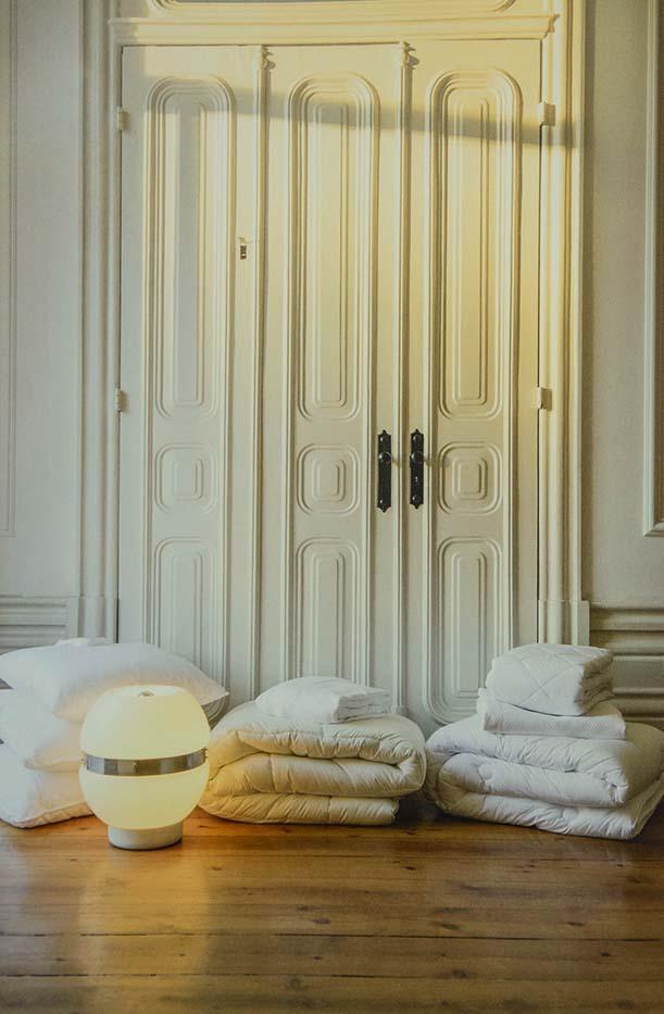 Edredons i roba de llit blancs sobre sòl de fusta