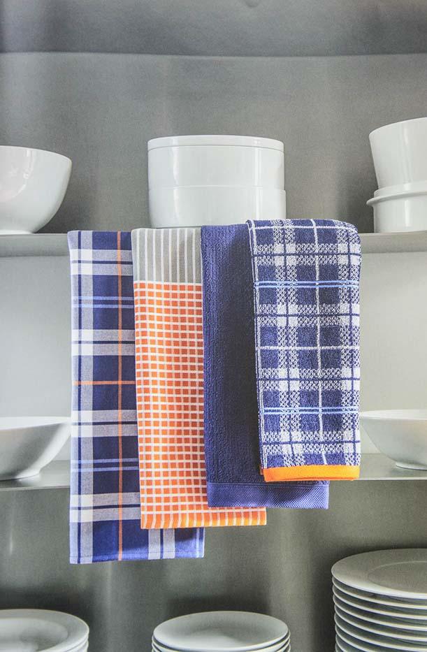 Draps de cuina de colors en armari de rebost amb vaixella blanca