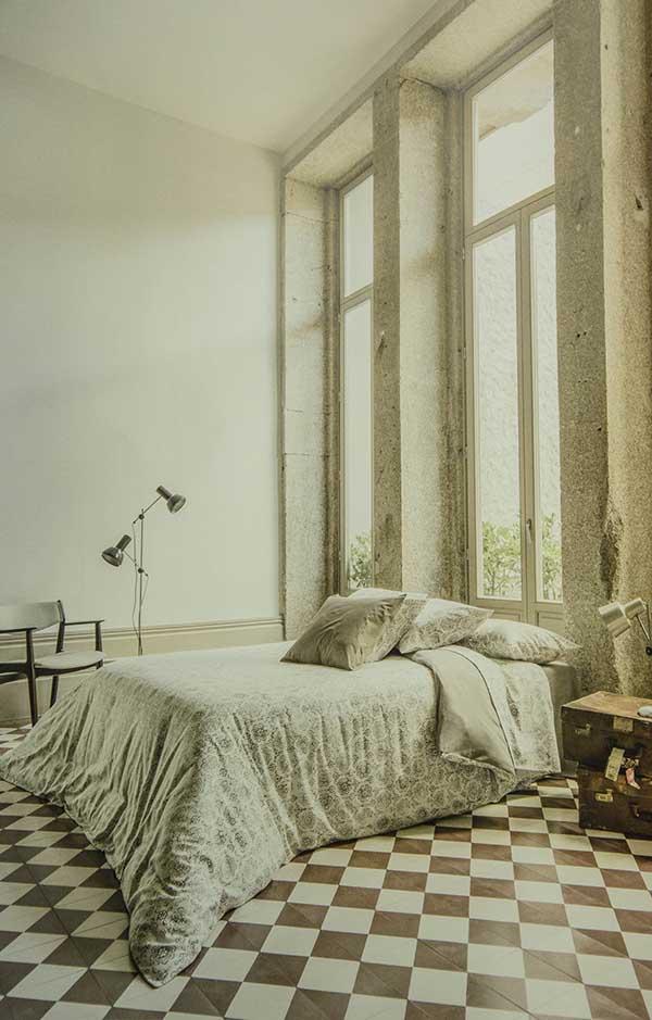 Cama con edredón y cojines, ventanas hasta el techo y luz natural