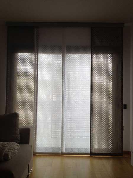 Salón con suelo de parquet, un sofá con cojines y ventana grande con un panel japonés
