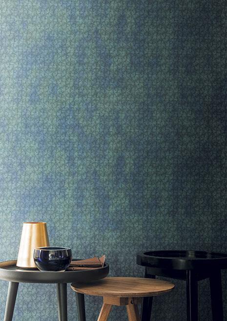 Paret amb paper pintat en blaus i verds amb textura. Taules baixes de fusta amb gerros.