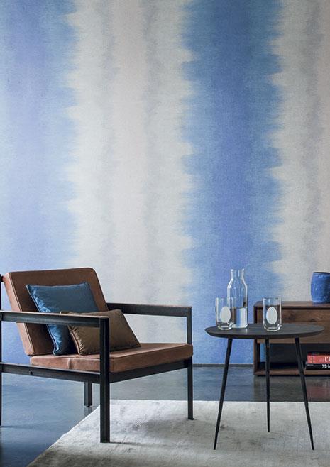 Paret de colors blaus i blancs, sill´pn amb coixins i taula baixa amb gots i una ampolla sobre catifa blanca.