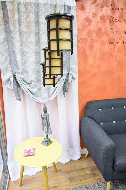 Escaparate de tienda con una mesa baja, sofá, cortinas y lámpara estilo farol