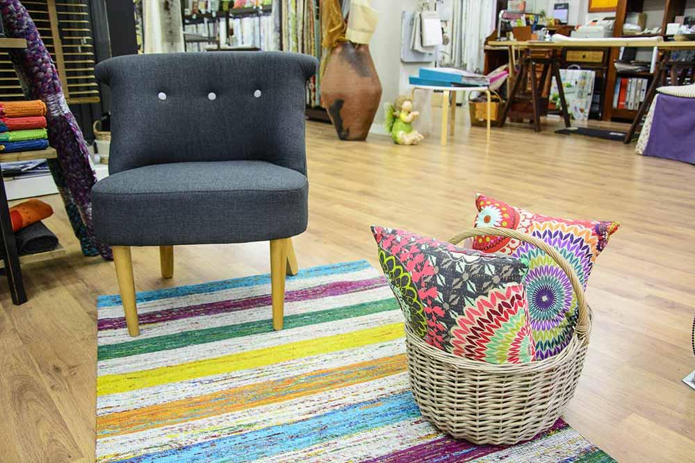 Interior de tienda con alfombra, sofá de una plaza y cesta de mimbre con cojines estampados en diferentes colores