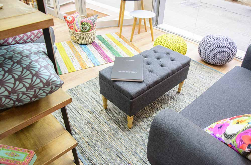 Escaparate de tienda con alfombra, sofá de una plaza, reposa pies, bancos, cesta de mimbre con cojines estampados en diferentes colores.