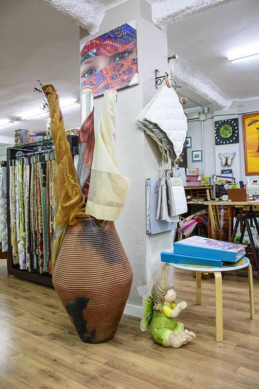 Interior de tienda con jarrón de gran tamaño con rollos de telas en su interior. De fondo muestrario de teles colgadas en vertical.