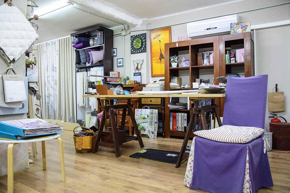 Interior de Tienda con mesa de trabajo en madera, silla forrada en tela y cojín. De fondo estantería con artículos de decoración y muestrario de telas colgadas en vertical.