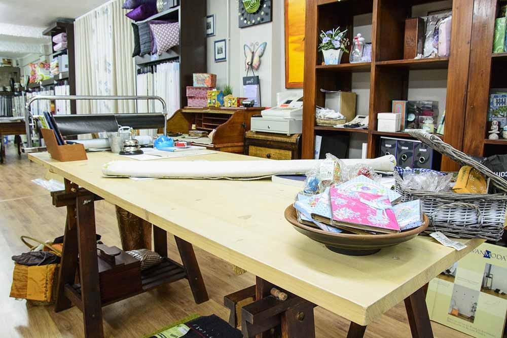 Interior de Tienda con mesa de trabajo de madera en primer plano, con telas y herramientas para corte. De fondo estantería con artículos de decoración y muestrario de telas colgadas en vertical.
