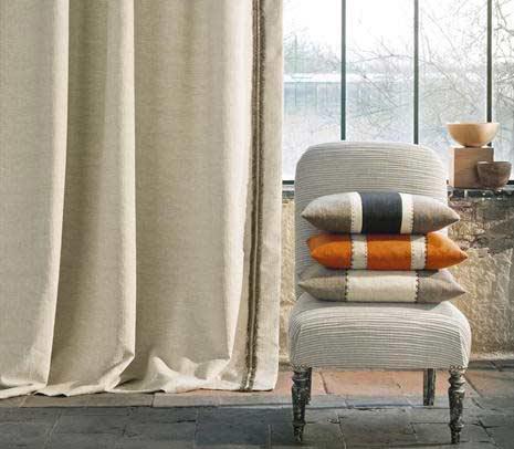 Butaca amb tres coixins de colors càlids fons finestra cortina tradicional