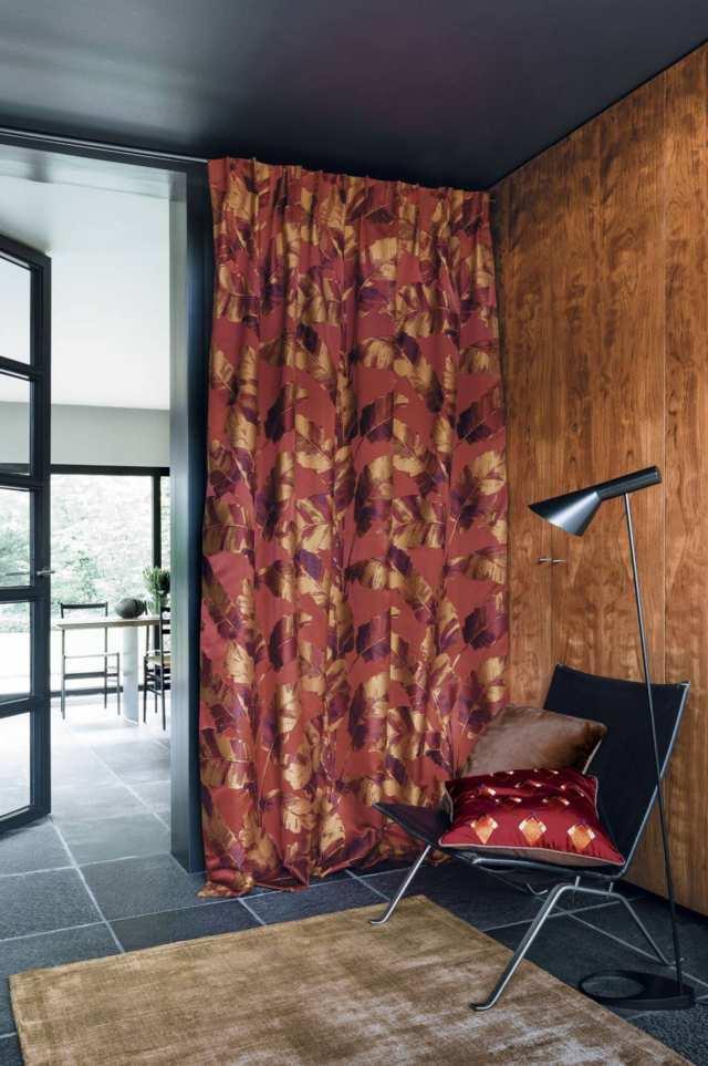 Cortinas fruncidas marca Casamance en tonos marrones con silla y alfombra delante de fondo imágenes de ventanas