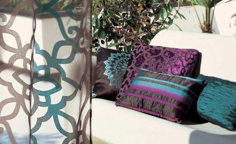Cortinas Visillos transparentes con estampados de color marrón y turquesa de fondo sofá blanco con cojines oscuros