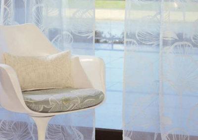 Cortines Visillos transparents en primer pla cadira blanca de plàstic vintage amb dos coixins marrons