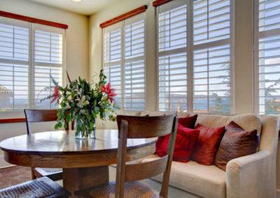 Saló amb cortines venecianes de fusta blanques taula i cadires de fusta marró sofà clar amb coixins vermells