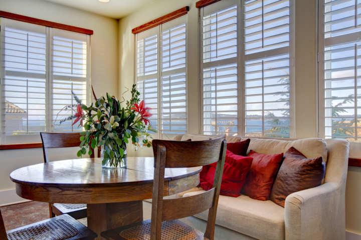 Salón con cortinas venecianas de madera blancas mesa y sillas de madera marrón sofá claro con cojines rojos