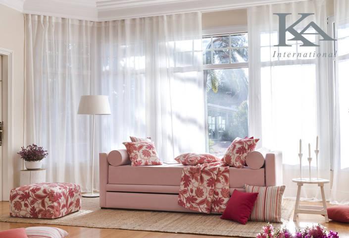 Salón en tonos rojos y pastel con cortina convencionales sofá y cojines
