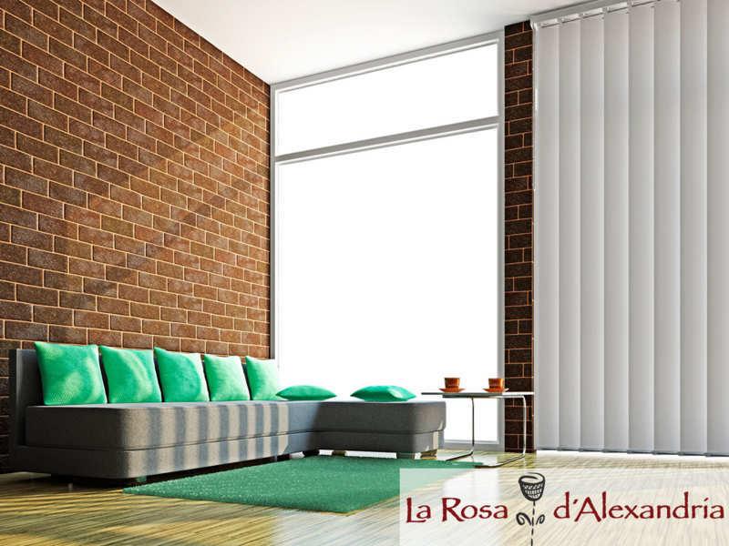 salón moderno ventanal con cortinas verticales pared de ladrillo, sofá, moqueta y suelo de madera