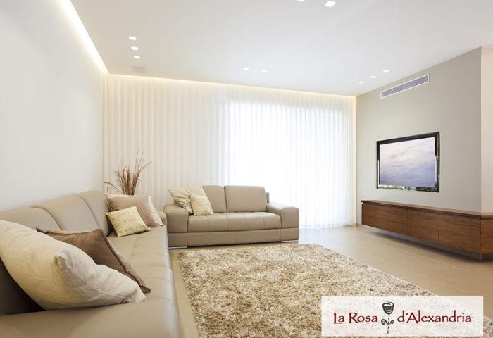 Salón con sofá moqueta y cortinas verticales a medida