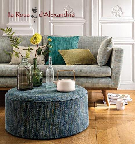 Colores y texturas en cortinas, tapizados y decoración de salón con sillón, cojines y suelo de parquet