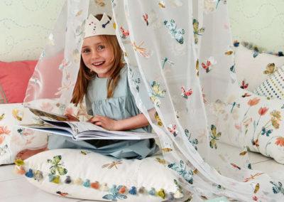 habitaciones infantiles niña con corona leyendo y cortinas de mariposas cojines a juego