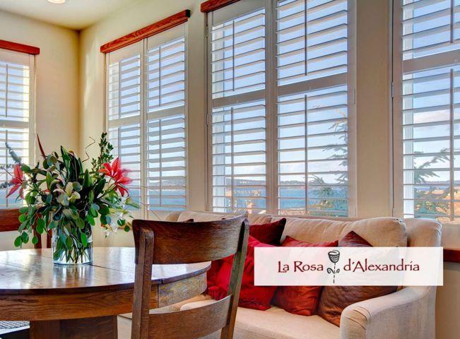 Ventana con cortina veneciana mesa con jarrón y logo de variedad en cortinas La Rosa d'Alexandría